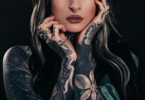 Woman-showing-body-tattoo-while-holding-her-face